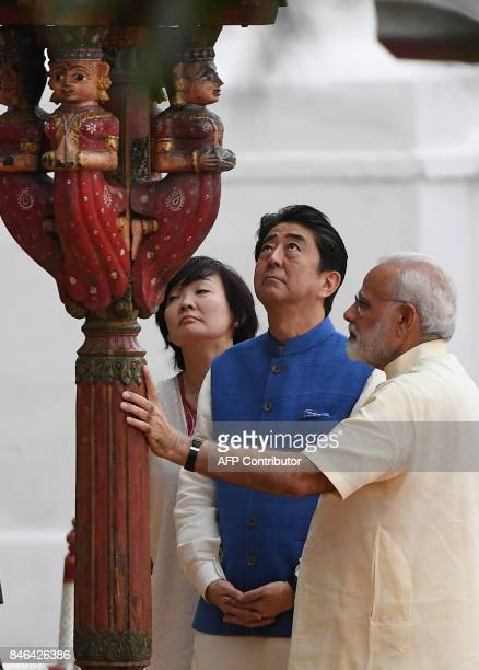 Indian Prime Minister Narendra Modi shows a wooden pillar to Japanese Prime Minister Shinzo Abe and his wife Akie Abe during their visit to Sabarmati...