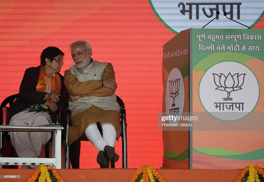 Indian Prime Minister <a gi-track='captionPersonalityLinkClicked' href=/galleries/search?phrase=Narendra+Modi&family=editorial&specificpeople=822611 ng-click='$event.stopPropagation()'>Narendra Modi</a> (R) speaks with Bharatiya Janata Party (BJP) Delhi chief ministerial candidate <a gi-track='captionPersonalityLinkClicked' href=/galleries/search?phrase=Kiran+Bedi&family=editorial&specificpeople=2886102 ng-click='$event.stopPropagation()'>Kiran Bedi</a> (L) during a public rally in New Delhi on February 3, 2015. Indian Prime Minister <a gi-track='captionPersonalityLinkClicked' href=/galleries/search?phrase=Narendra+Modi&family=editorial&specificpeople=822611 ng-click='$event.stopPropagation()'>Narendra Modi</a> has stepped up an offensive against Delhi opponent and anti-graft campaigner Arvind Kejriwal as India's capital prepares to holds state elections.