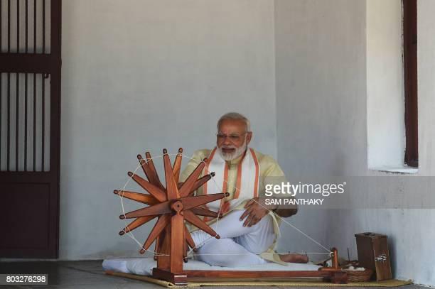 Indian Prime Minister Narendra Modi spins a yarn on a charkha during his visit to Mahatma Gandhi's Sabarmati Ashram in Ahmedabad on June 29 2017 Modi...
