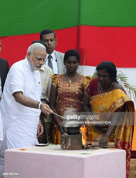 Indian Prime Minister Narendra Modi takes part in a milk boiling ceremony as he handed over Indianfunded houses to Tamils displaced or made destitute...