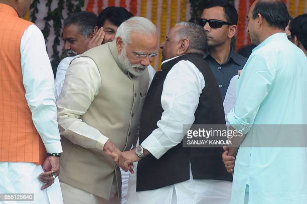 Indian Prime Minister Narendra Modi talks to Samajwadi party leader Mulayam Singh Yadav during Yogi Adityanath's swearingin ceremony as the Uttar...