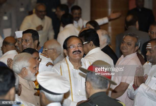 Indian Prime Minister Narendra Modi talks to the newly swornin Indian Vice President Venkaiah Naidu as they leave the presidential palace after the...