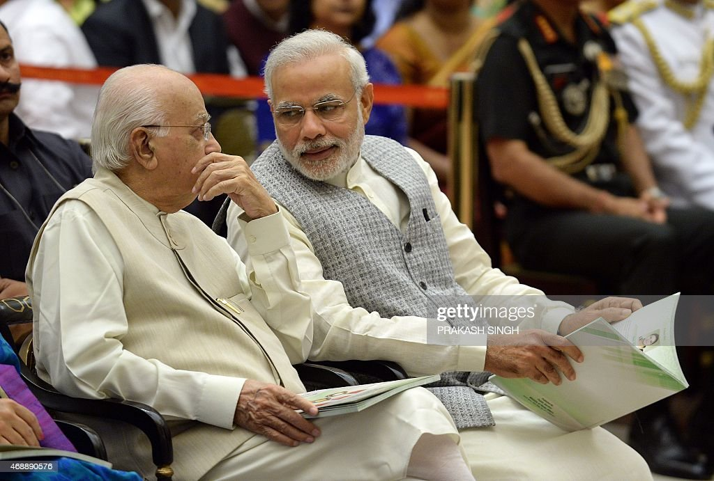 Indian Prime Minister <a gi-track='captionPersonalityLinkClicked' href=/galleries/search?phrase=Narendra+Modi&family=editorial&specificpeople=822611 ng-click='$event.stopPropagation()'>Narendra Modi</a> (R) talks with senior Bhartiya Janta Party (BJP) leader L. K. Advani during a Civil Investiture Ceremony at Rashtrapati Bhavan in New Delhi on April 8, 2015. AFP PHOTO/ PRAKASH SINGH