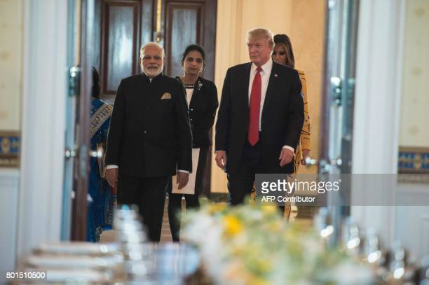 Indian Prime Minister Narendra Modi US President Donald Trump and First Lady Melania Trump arrive in the Blue Room for dinner at the White House in...
