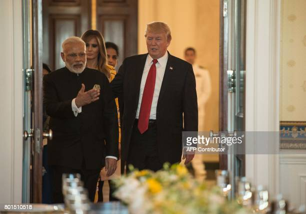 Indian Prime Minister Narendra Modi US President Donald Trump and First Lady Melania Trump sit for dinner in the Blue Room at the White House in...