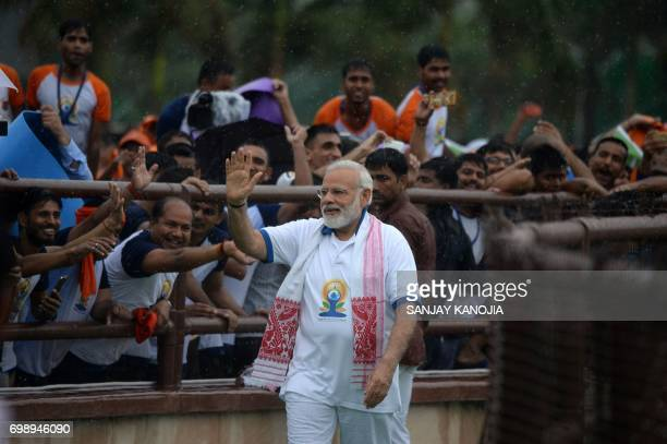 Indian Prime Minister Narendra Modi waves as he greets yoga practitioners during a mass yoga session to mark the third International Yoga Day at...