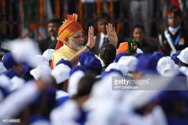 Indian Prime Minister Narendra Modi waves to children participating in the country's 71st Independence Day celebrations which marks the 70th...