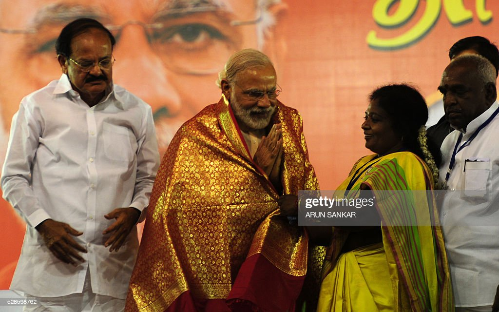 Indian Prime Minister Narendra Modi(C)is watched by Parliamentary Affairs Minister Venkaiah Naidu(L) as he is garlanded by Tamil Nadu BJP president Tamilisai Sounderajan(R) ahead of his address to an election rally of Bharatiya Janata Party(BJP)supporters at The YMCA Grounds in Chennai on May 6, 2016, ahead of voting in state assembly elections in the southern Indian state of Tamil Nadu. / AFP / ARUN
