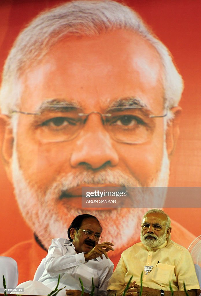 Indian Prime Minister Narendra Modi(R)speaks with Parliamentary Affairs Minister Venkaiah Naidu as he prepares to address an election rally of Bharatiya Janata Party(BJP)supporters at The YMCA Grounds in Chennai on May 6, 2016, ahead of voting in state assembly elections in the southern Indian state of Tamil Nadu. / AFP / ARUN