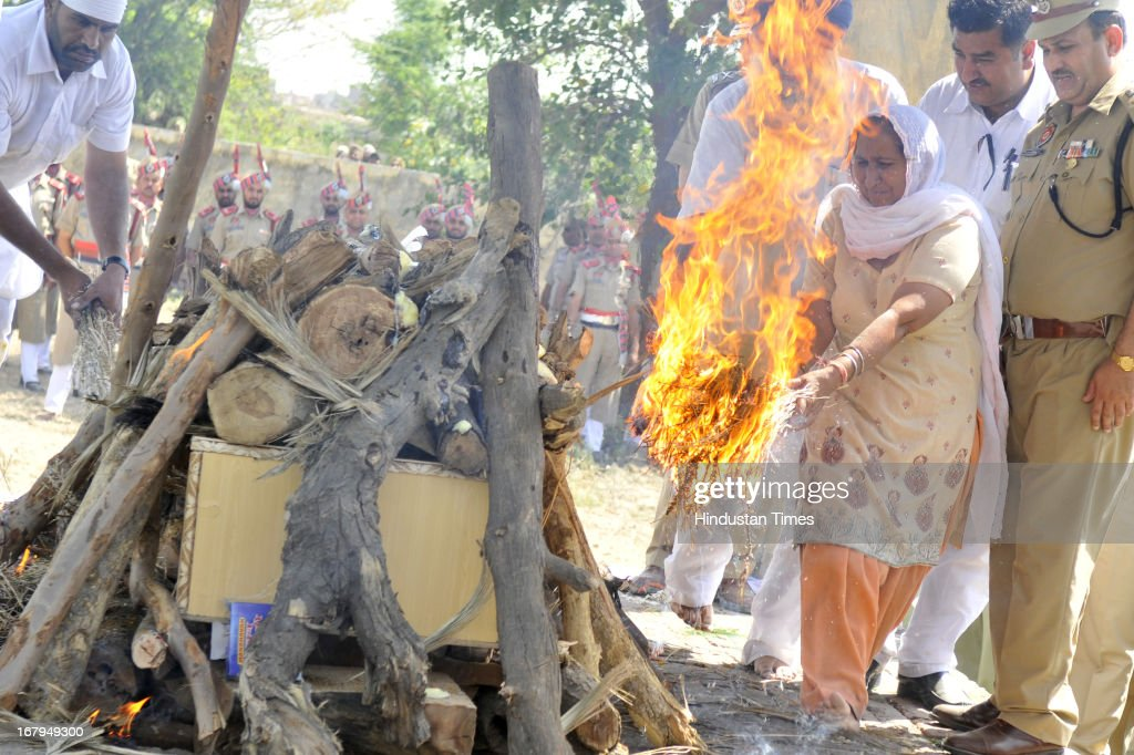 Indian prisoner Sarabjit Singh's sister Dalbir Kaur lit the pyre of his brother Sarabjit during his last rights at his native village Bikhiwind on May 3, 2013 about 40 Kms from Amritsar, India. Sarabjit Singh, an Indian prisoner in Pakistan who died after being brutally assaulted in a Pakistani jail, was cremated in his native village with full state honours.