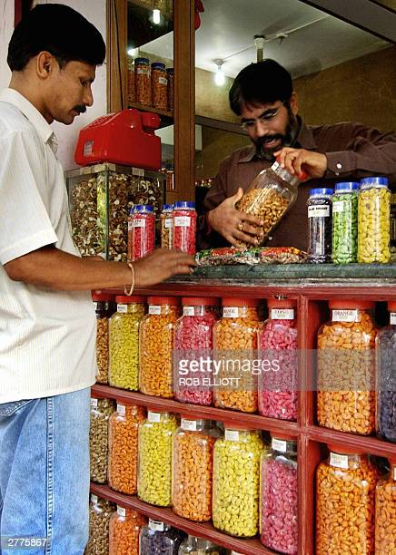 Indian proprietor Asok Hirawi of Royal Kajuwala opens a container of coated coloured cashew nuts for a customer to sample at a shop in Goa 615 kms...
