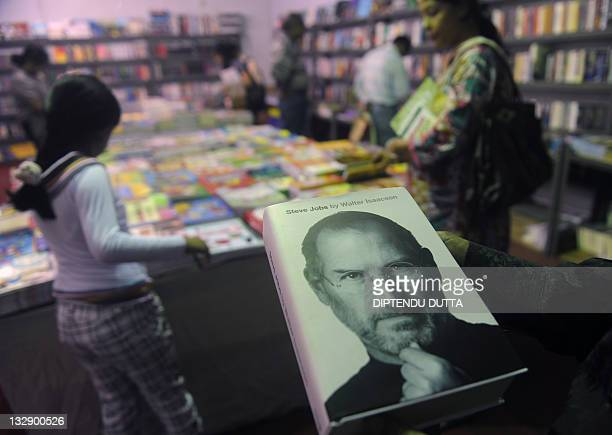 Indian prospective buyers look at books near the new biography of Apple cofounder Steve Jobs at Siliguri Book fair in Siliguri on November 15 2011...