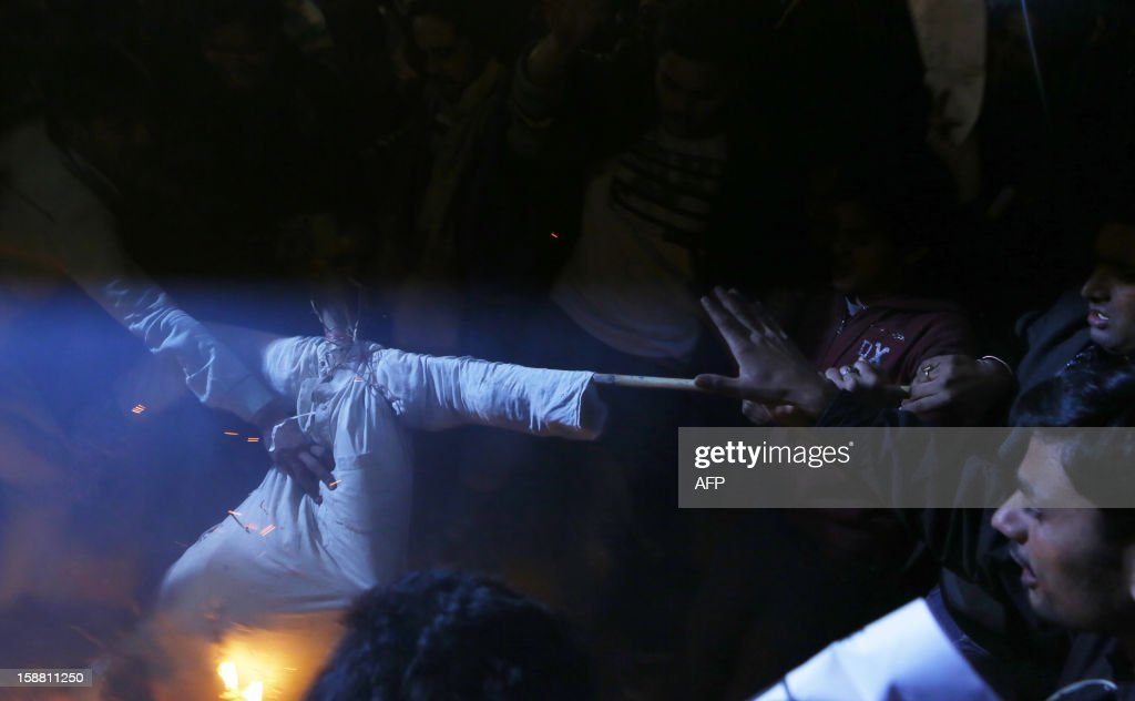 Indian protesters beat an effigy depicting rapists as it burns during a rally in New Delhi on December 30, 2012, following the cremation of a gangrape victim in the Indian capital. The victim of a gang-rape and murder which triggered an outpouring of grief and anger across India was cremated at a private ceremony, hours after her body was flown home from Singapore. A student of 23-year-old, the focus of nationwide protests since she was brutally attacked on a bus in New Delhi two weeks ago, was cremated away from the public glare at the request of her traumatised parents. AFP PHOTO/ ANDREW CABALLERO-REYNOLDS