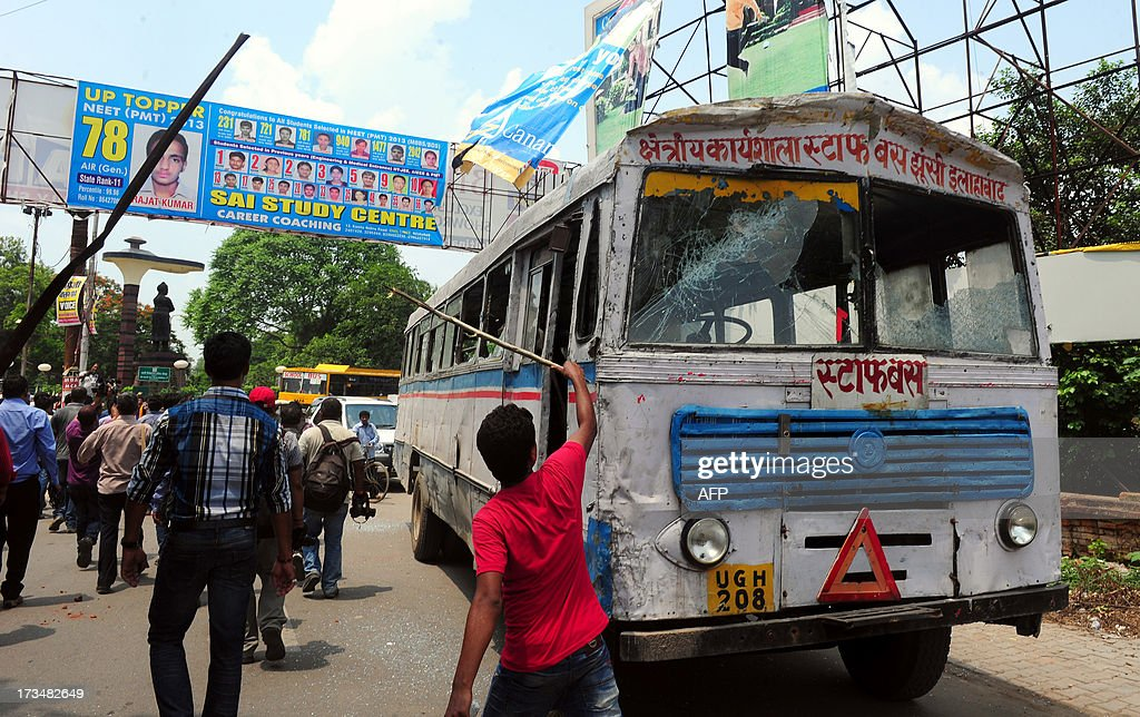 Indian protesters damage a bus during a protest against reservation for Other Backward Classes (OCC) candidates in the Uttar Pradesh Public Service Commission, in Allahabad on July 15, 2013.