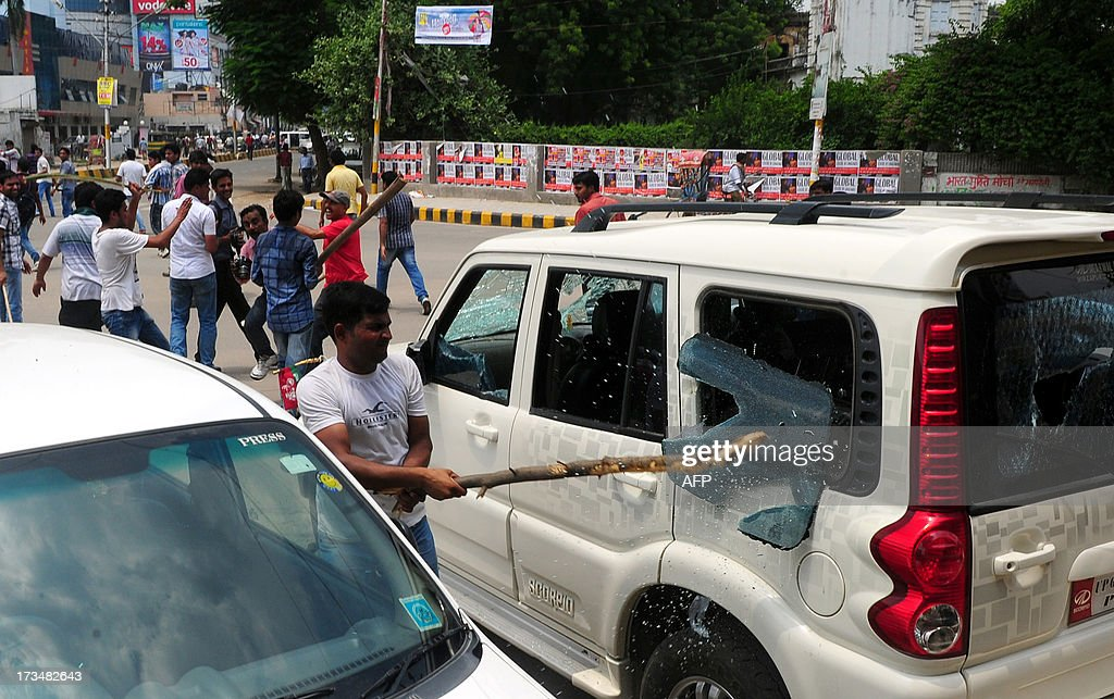 Indian Protesters damage a car during a protest against reservation for Other Backward Classes (OCC) candidates in the Uttar Pradesh Public Service Commission, in Allahabad on July 15, 2013. AFP PHOTO/ SANJAY KANOJIA