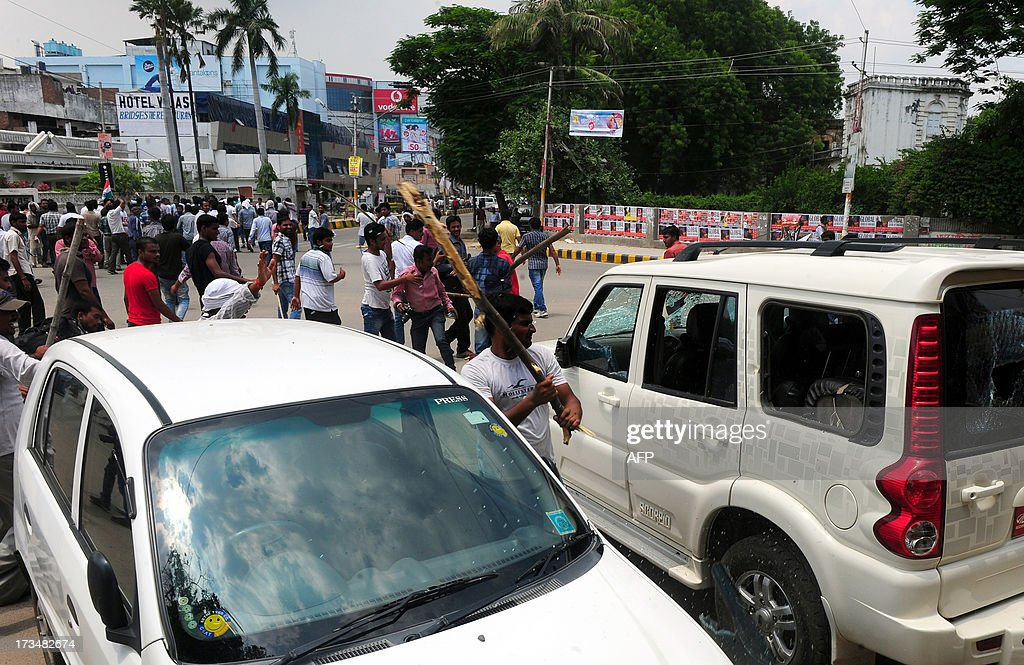 Indian protesters damage a car during a protest against reservation for Other Backward Classes (OCC) candidates in the Uttar Pradesh Public Service Commission, in Allahabad on July 15, 2013.