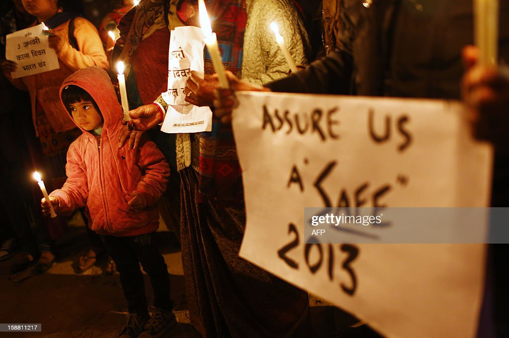 Indian protesters hold candles and placards during a rally in New Delhi on December 30, 2012, following the cremation of a gangrape victim in the Indian capital. The victim of a gang-rape and murder which triggered an outpouring of grief and anger across India was cremated at a private ceremony, hours after her body was flown home from Singapore. A student of 23-year-old, the focus of nationwide protests since she was brutally attacked on a bus in New Delhi two weeks ago, was cremated away from the public glare at the request of her traumatised parents.