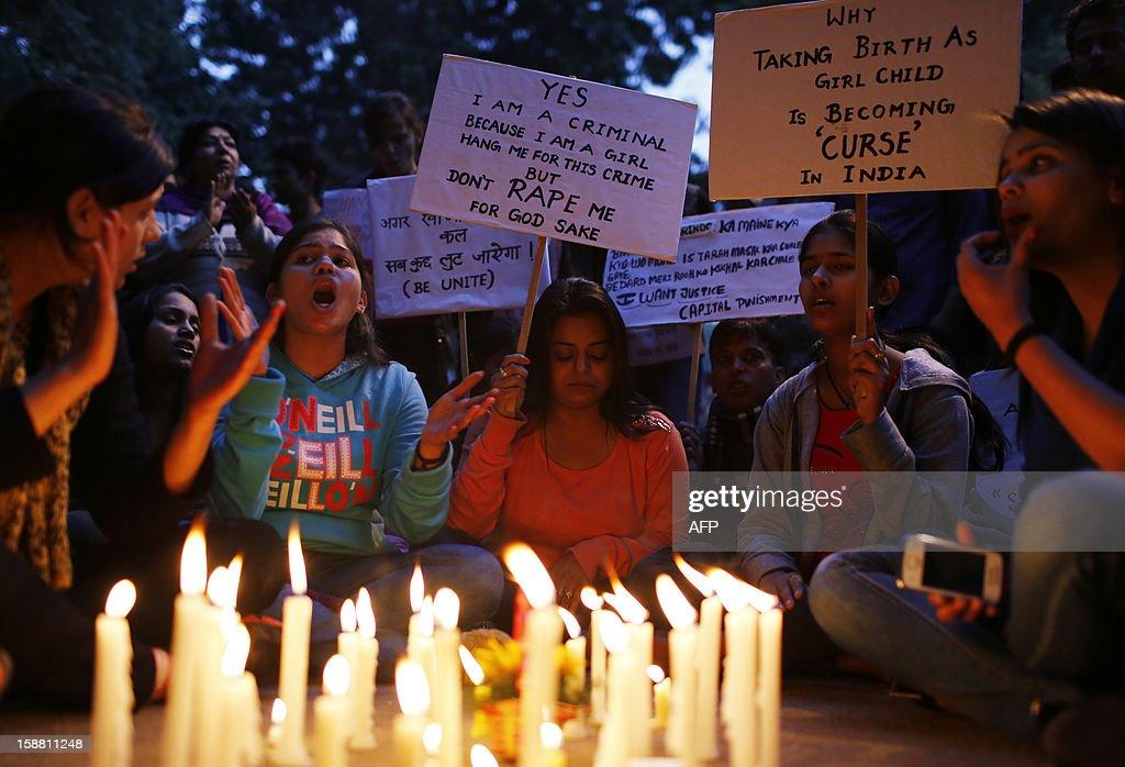 Indian protesters hold candles and placards during a rally in New Delhi on December 30, 2012, following the cremation of a gangrape victim in the Indian capital. The victim of a gang-rape and murder which triggered an outpouring of grief and anger across India was cremated at a private ceremony, hours after her body was flown home from Singapore. A student of 23-year-old, the focus of nationwide protests since she was brutally attacked on a bus in New Delhi two weeks ago, was cremated away from the public glare at the request of her traumatised parents. AFP PHOTO/ ANDREW CABALLERO-REYNOLDS