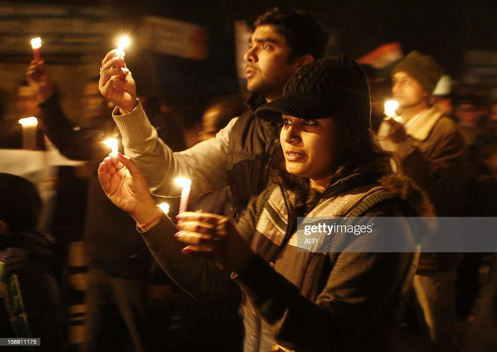 Indian protesters hold candles during a rally in New Delhi on December 30, 2012, following the cremation of a gangrape victim in the Indian capital. The victim of a gang-rape and murder which triggered an outpouring of grief and anger across India was cremated at a private ceremony, hours after her body was flown home from Singapore. A student of 23-year-old, the focus of nationwide protests since she was brutally attacked on a bus in New Delhi two weeks ago, was cremated away from the public glare at the request of her traumatised parents. AFP PHOTO/ ANDREW CABALLERO-REYNOLDS