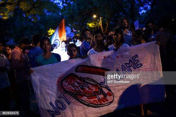 TOPSHOT Indian protesters hold placards as they gather during a 'Not in my name' silent protest at Jantar Mantar in New Delhi on June 28 following a...