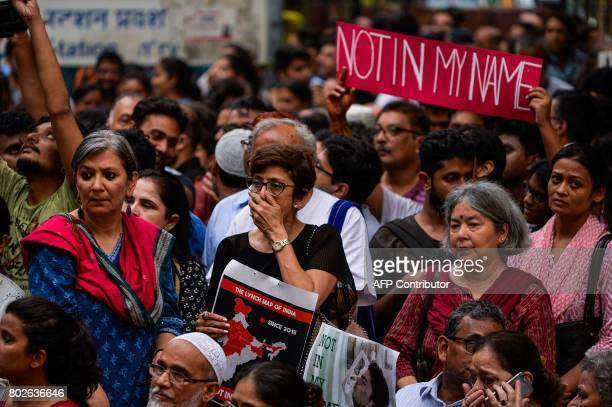 Indian protesters hold placards as they gather for a 'Not in my name' silent protest at Jantar Mantar in New Delhi on June 28 following a spate...
