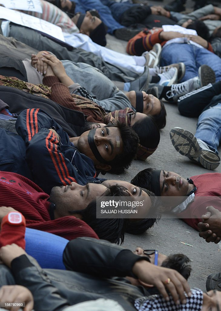 Indian protestors lie on a road during a protest in New Delhi on December 29, 2012, after the death of a gangrape victim from the Indian capital. Indian leaders appealed for calm and security forces headed off fresh unrest by turning New Delhi into a fortress after a student who was savagely gang-raped died in a Singapore hospital. Police threw a ring of steel around the centre of the Indian capital after news of the 23-year-old medical student's death was broken in the early hours by the Singapore hospital that had been treating her for the last two days.