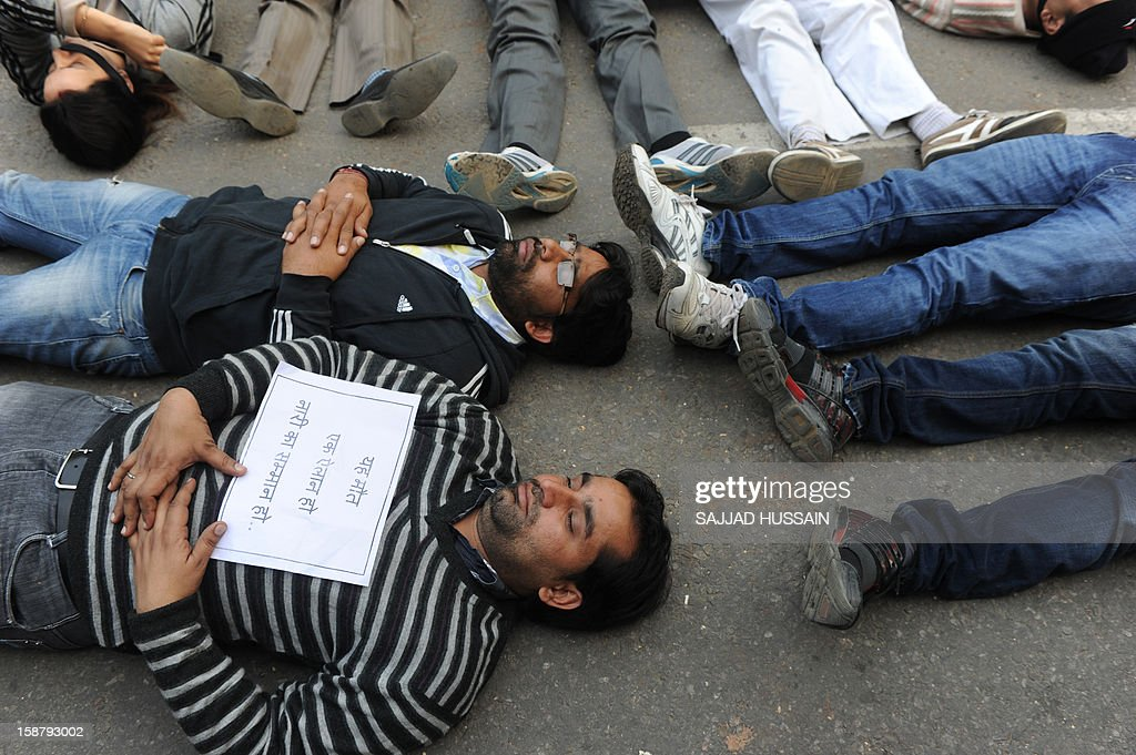 Indian protestors lie on a road during a protest in New Delhi on December 29, 2012, after the death of a gangrape victim from the Indian capital. Indian leaders appealed for calm and security forces headed off fresh unrest by turning New Delhi into a fortress after a student who was savagely gang-raped died in a Singapore hospital. Police threw a ring of steel around the centre of the Indian capital after news of the 23-year-old medical student's death was broken in the early hours by the Singapore hospital that had been treating her for the last two days. AFP PHOTO/SAJJAD HUSSAIN