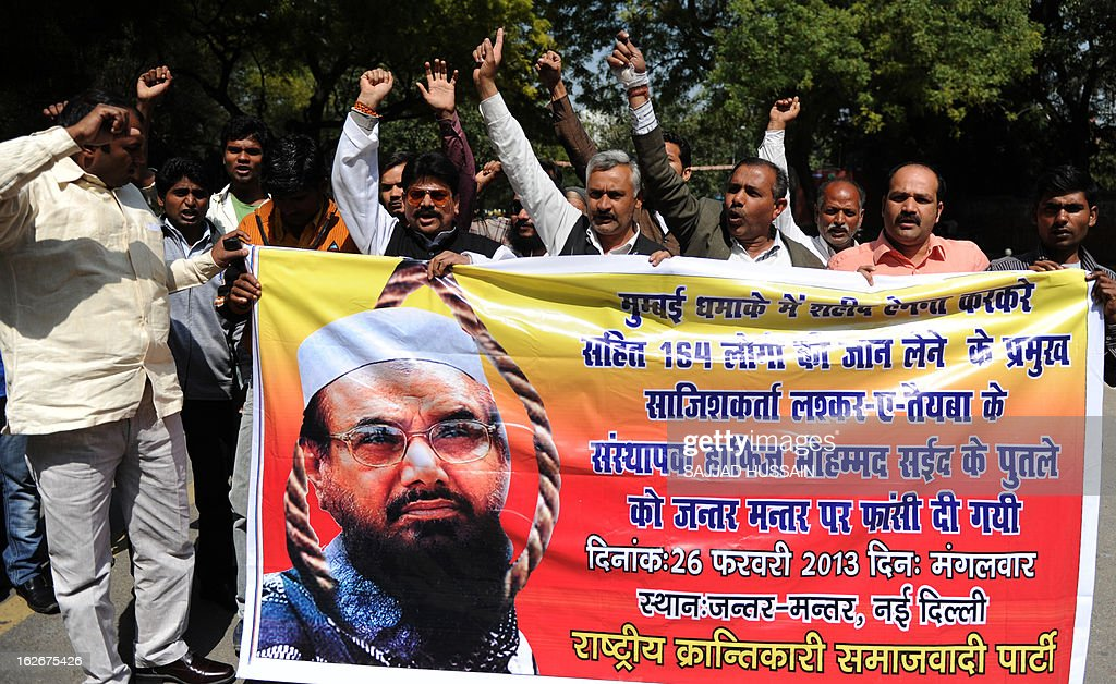 Indian protestors shout slogans as they hold a poster featuring the head of banned Pakistani charity Jamat ud Dawa, Hafiz Saeed during a protest in New Delhi on February 26, 2013. Protestors were demanding that Hafiz Syed be brought to India and hanged in the same manner as Ajmal Kasab, the only terrorist captured alive after the 2008 Mumbai attacks and Kashmiri separatist Afzul Guru, who was involved in a deadly attack on the Indian parliament in 2001.