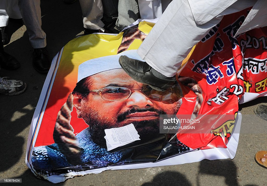 Indian protestors step on a poster featuring the head of banned Pakistani charity Jamat ud Dawa, Hafiz Saeed during a protest in New Delhi on February 26, 2013. Protestors were demanding that Hafiz Syed be brought to India and hanged in the same manner as Ajmal Kasab, the only terrorist captured alive after the 2008 Mumbai attacks and Kashmiri separatist Afzul Guru, who was involved in a deadly attack on the Indian parliament in 2001. AFP PHOTO/SAJJAD HUSSAIN
