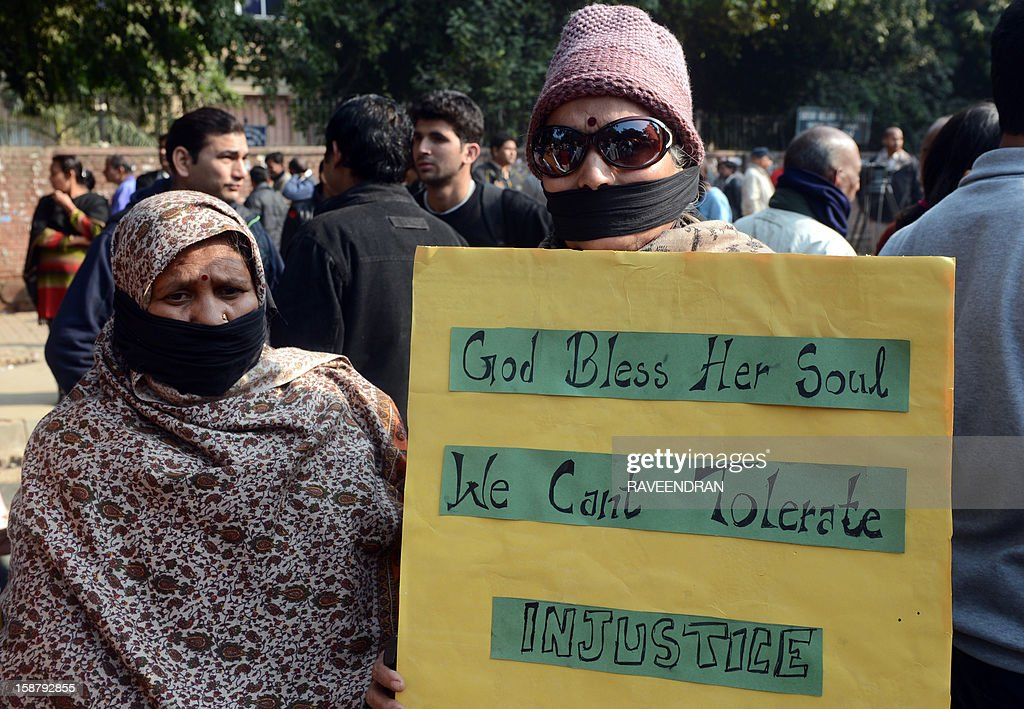Indian protestors their faces bound with black tape hold a placard during a protest demanding better security for women in New Delhi on December 29, 2012, as Indian leaders appealled for calm fearing fresh outbursts of protests after the death of a gang-rape student victim. New Delhi's top police officer and chief minister have urged people to mourn the death of a gang-rape victim in a peaceful manner as large parts of the city-centre were sealed off. The calls for calm came after an Indian woman who was gang-raped on a New Delhi bus died in a Singapore hospital after suffering severe organ failure.