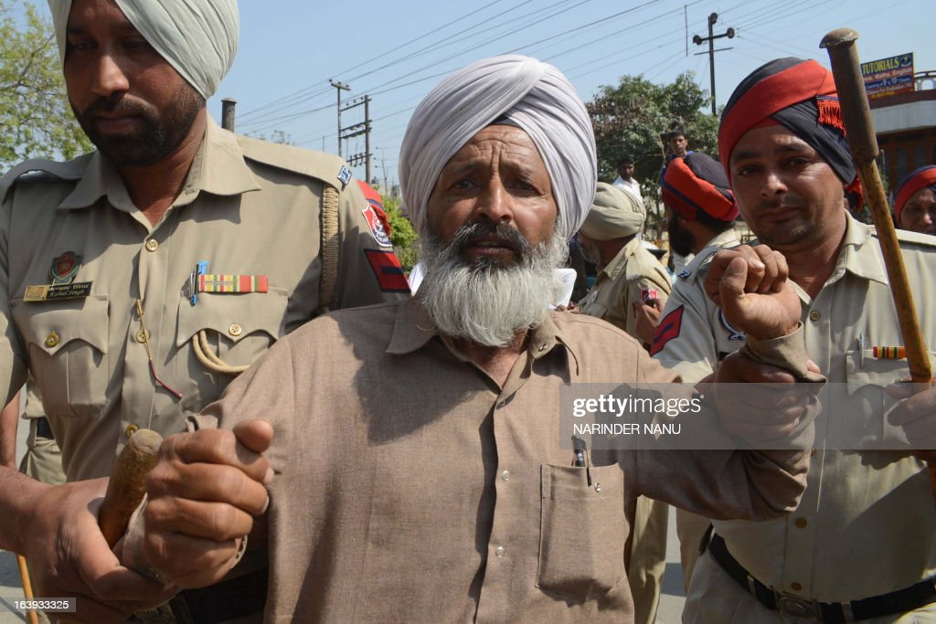 Indian Punjab police personnel detain a farmer marching towards the Amritsar Deputy Commissioner office in Amritsar on March 18, 2013. Indian Punjab police personnel arrested scores of farmers who were protesting perceived anti-farmer policies imposed by the state government, and demanding the cancellation of a police case against farmers held for the alleged murder of a Punjab Police assistant sub-inspector at Tarn Taran.