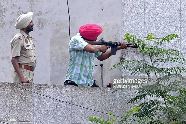 Indian Punjab police personnel fire during an encounter with armed attackers at the police station in Dinanagar town in the Gurdaspur district of...