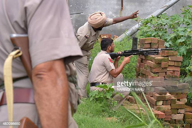Indian Punjab police personnel take position during an encounter with armed attackers at the police station in Dinanagar town in the Gurdaspur...
