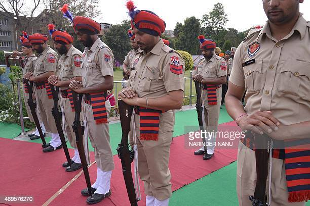 Indian Punjab police present arms as they pay tribute on the 96th anniversary of the Jallianwala Bagh massacre at the memorial in Amritsar on April...