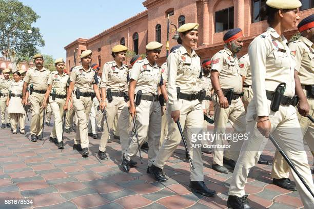 Indian Punjab police walk during a foot patrol in Amritsar on October 16 2017 Security has been increased around the country ahead of the Hindu...