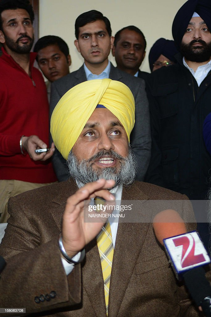 Indian Punjab state Deputy Chief Minister Sukhbir Singh Badal (C) addresses the media after meeting with family members of late Indian Punjab Police assistant sub-inspector Ravinder Pal Singh at his resident in Rampura village on the outskirts of Amritsar on December 10, 2012. The leader of Punjab's ruling Shiromani Akali Dal and an accomplice were arrested on December 6, 2012, for allegedly killing the police official Ravinder Pal Singh.