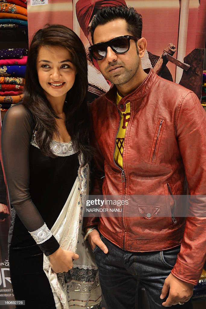 Indian Punjabi actor Gippy Grewal (R) and actress Surveen Chawla pose after attending a press conference in Amritsar on February 4, 2013. The actors visited the city as part of a promotional tour of their upcoming film ' Singh vs Kaur' directed by Navaniat Singh.