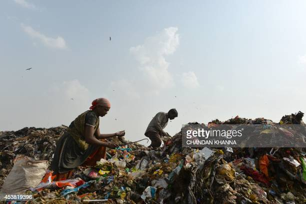Indian rag pickers sort through garbage for recyclable materials at the Ghazipur landfill site in the east of New Delhi on August 19 2014 The...