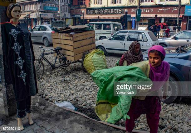 Indian rag pickers walk past a mannequin in a market on November 06 2017 in Srinagar the summer capital of Indian administered Kashmir India Markets...