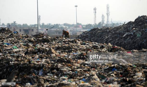 A Indian ragpicker walks through a garbage dump during Earth Day on the outskirts of Chennai on April 22 2017 Earth Day is marked on April 22 to...