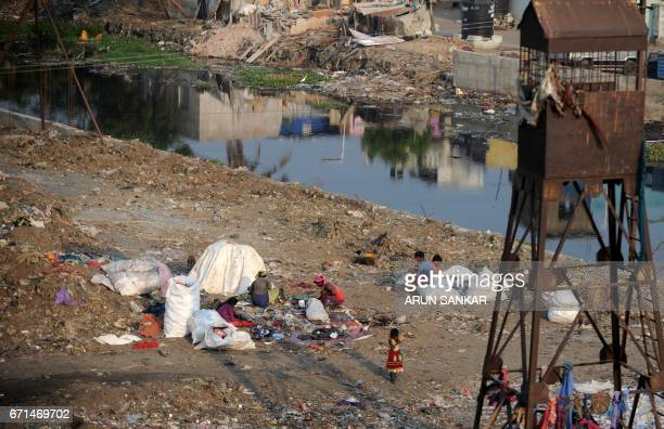 Indian ragpickers look for useables items at a garbage dump during Earth Day on the outskirts of Chennai on April 22 2017 Earth Day is marked on...