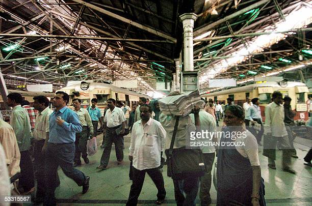 Indian railway commuters walk on a platform at Chatrapati Shivaji Terminus in Mumbai 02 August 2005 after enduring a weeklong deluge which killed...
