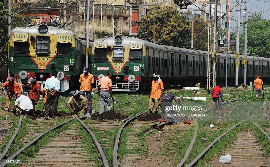 Indian railway employees work on the tracks at a railway station in Kolkata on February 26, 2013, as Railway Minister Pawan Kumar Bansal unveiled the railway budget in parliament. The railway, the country's largest employer with some 1.4 million people on its payroll, runs 11,000 passenger and freight trains and carries 19 million people daily.