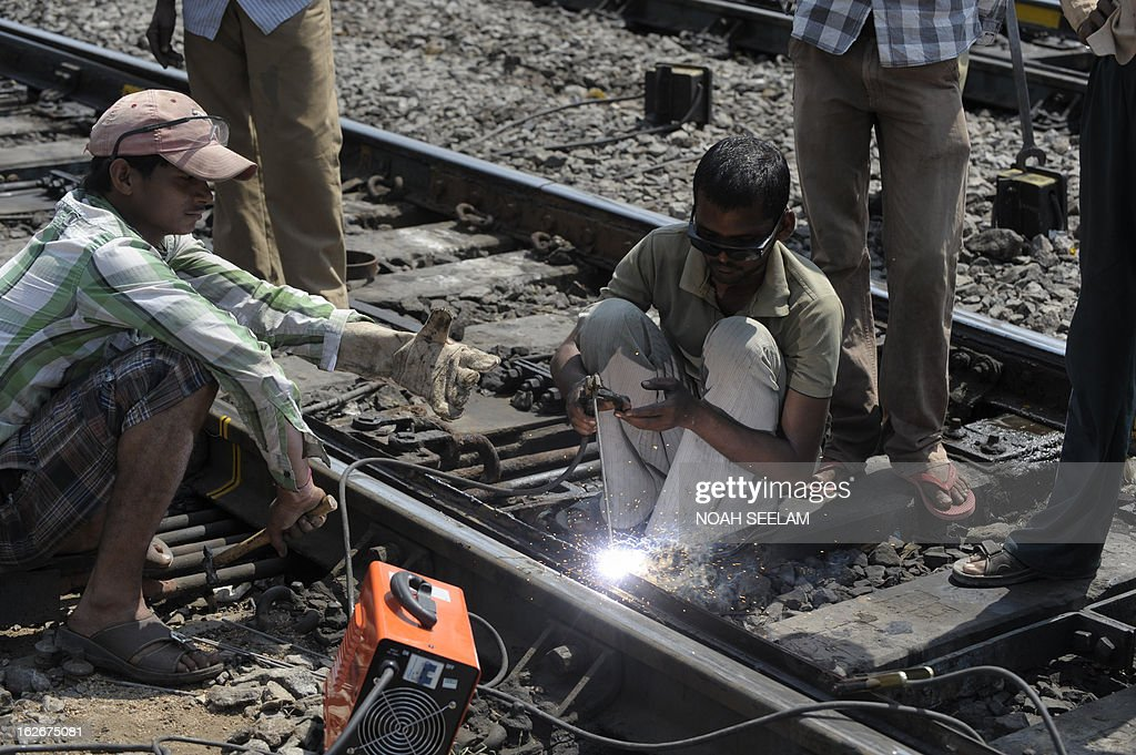 Indian railway emplyees repair the tracks at a railway station in Hyderabad on February 26, 2013 as Railway Minister Pawan Kumar Bansal unveiled the railway budget in parliament. The railway, the country's largest employer with some 1.4 million people on its payroll, runs 11,000 passenger and freight trains and carries 19 million people daily. AFP PHOTO / Noah SEELAM