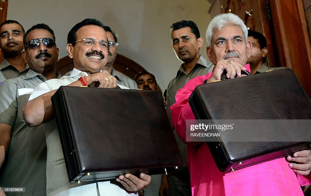 Indian Railway Minister D V Sadananda Gowda (L) and Minister of State for Railway, Manoj Singha hold up their briefcases at Parliament before presenting the railway budget in New Delhi on July 8, 2014. India's new government is expected to suggest a bigger private sector role in developing the nation's railway as it presents its bellwether budget on July 8 for the colonial-era train network.
