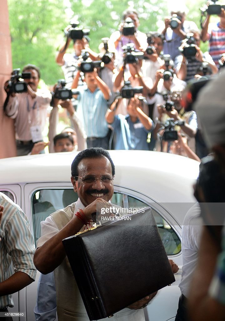 Indian Railway Minister D V Sadananda Gowda holds up his briefcase as he walks towards Parliament before presenting the railway budget in New Delhi on July 8, 2014. India's new government is expected to suggest a bigger private sector role in developing the nation's railway as it presents its bellwether budget on July 8 for the colonial-era train network.