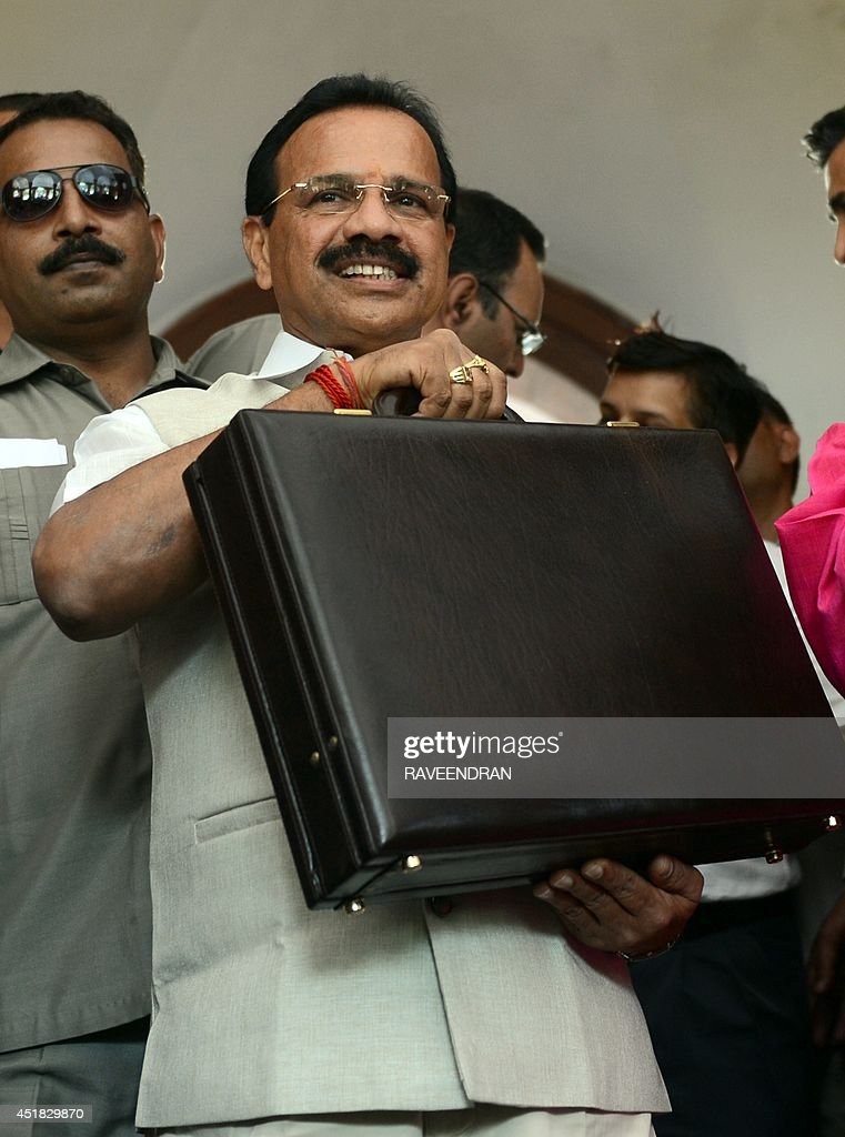 Indian Railway Minister D V Sadananda Gowda holds up his briefcase as he walks towards Parliament before presenting the railway budget in New Delhi on July 8, 2014. India's new government is expected to suggest a bigger private sector role in developing the nation's railway as it presents its bellwether budget on July 8 for the colonial-era train network.AFP PHOTO/RAVEENDRAN