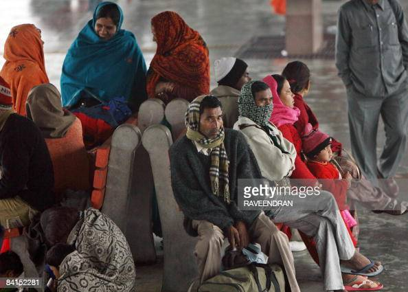 Indian railway passengers gather on a platform at New Delhi Railway Station in New Delhi on January 1 as they await the arrival of delayed trains...