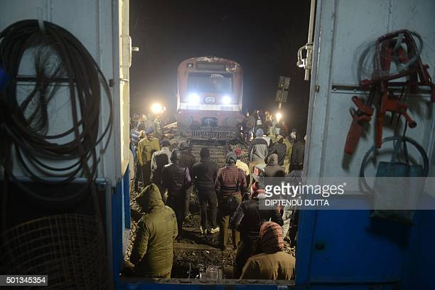 Indian railway personnel work to restore service to a derailed passenger train after it collided with a female elephant in the Gulma area inside the...