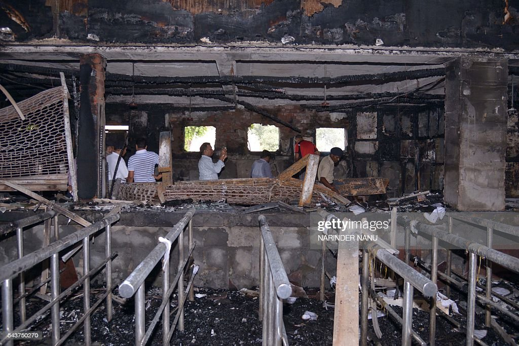 Indian Railway Protection Force (RPF) personnel inspect the site after a fire burnt down the railway reservation booking counters at the railway station in Amritsar on June 30, 2016. The fire was allegedly caused due to a short circuit, officials said / AFP / NARINDER